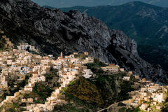 View in amphitheater of the village of Olympos from Mount Profitis Ilias. Hanging on a ridge of a peak the house of Olympos descend in cascades towards a small Royalty Free Stock Image
