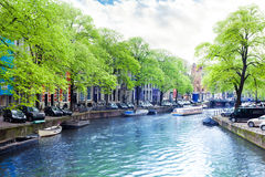 View of Amsterdam canal and houses facades. Beautiful view of Amsterdam canal and building facades during summer time with cloudy sky Royalty Free Stock Photography