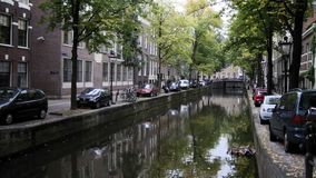 View of Amsterdam city: early morning, cloudy day, Autumn - cars and bicycles parked along the canal - Netherlands. Wide angle stock video footage