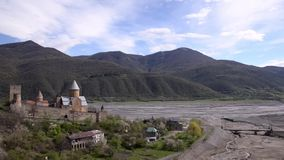 View Ananuri fortress on background not deep river, spring verdant mountains and blue sky with clouds. Georgia stock footage