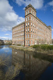 Victorian industrial building. View of the Anchor Mills building, Paisley, Scotland, showing its reflection on the river Cart. Formerly a domestic finishing mill Stock Image