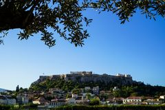 View of the ancient Acropolis from Monastiraki Square through old town buildings with olive tree foliage, focus on foreground Stock Photography