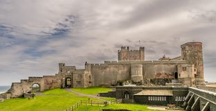 A view of an ancient castle on top of a grass hill. A castle from a bygone age on a grass hill. a view of castle from the beach. grey clouds gathering in the sky royalty free stock photo