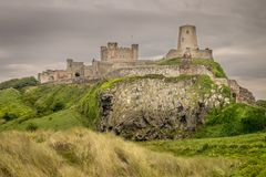 A view of an ancient castle on top of a grass hill. A castle from a bygone age on a grass hill. a view of castle from the beach. grey clouds gathering in the sky stock image