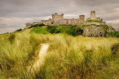 A view of an ancient castle on top of a grass hill. A castle from a bygone age on a grass hill. a view of castle from the beach. grey clouds gathering in the sky royalty free stock image