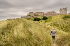A view of an ancient castle on top of a grass hill stock photo