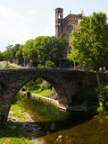 View of ancient church and bridge in Sant Joan les Fonts. View of ancient church and medieval bridge, built with volcanic stone in Sant Joan les Fonts. Catalonia Royalty Free Stock Photo