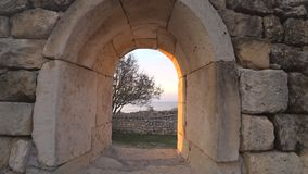 View of the ancient city through the window arch. Beautiful view of the ancient city near the sea through the window arch stock video