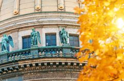 View of the ancient statues of stucco and the dome of St. Isaac`s Cathedral Petersburg autumn maple leaves. Stock Images