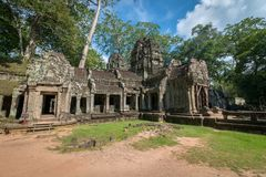 Ancient stone door with clear blue sky, Ta Prohm temple ruins, A. View of an ancient stone door with clear blue sky, Ta Prohm temple ruins, Angkor, Cambodia royalty free stock image