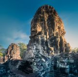 Sunrise view of ancient temple Bayon Angkor Wat. View of ancient temple Bayon Angkor Wat complex with stone faces of buddha and sun rays of sunrise Siem Reap royalty free stock images