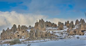 View of ancient Uchisar cave town and a castle of Uchisar dug from a mountains in Cappadocia, Central Anatolia,Turkey. Winter time with sun Royalty Free Stock Photography