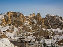 View of ancient Uchisar cave town and a castle of Uchisar dug from a mountains in Cappadocia, Central Anatolia,Turkey. Winter time with sun Stock Photos