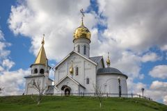 Ancient white stone orthodox church with golden domes. View of the Ancient white stone orthodox church with golden domes on the green grass hill royalty free stock photography