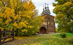 View of ancient wooden orthodox church circled by yellowed autumn trees, brown low fence and green lawn with yellow leaves on it stock image