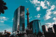 View of the angel of independence. The angel of independence with two buildings behind reflecting a blue sky with some clouds Royalty Free Stock Photo