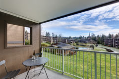 View from apartment balcony  of grassy hill and pool Stock Image