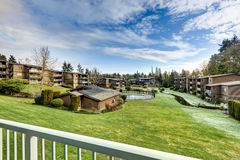 View from apartment balcony  of grassy hill and pool Stock Images