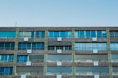 A view of apartment building top floors. Isolated on clean blue sky stock photography