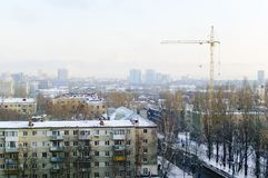 View of apartment houses from the top. Construction crane. Winter time royalty free stock photos
