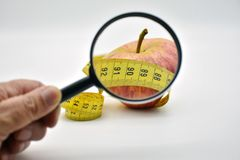 Apple wrapped with a tape measure royalty free stock photography