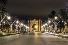 The view on Arc de Triomf from the park in evening. The view on Arc de Triomf from the park in evening, Barcelona, Spain. A lot of lights and perspective lines Royalty Free Stock Photo