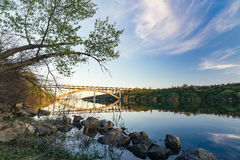 View of the arch bridge of Preobrazhensky. Sunset through the island of Khortitsa Stock Photos