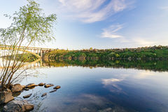 View of the arch bridge of Preobrazhensky. Sunset through the island of Khortitsa Stock Image