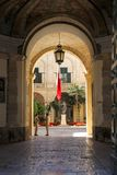 View from arch entrance of Grandmaster Palace Courtyard with maltese flag and two soldier in Valletta stock photography