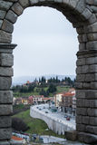 A view through the arch of famous ancient roman aqueduct of Segovia to town and streets Royalty Free Stock Images