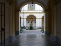 View through an arch of a formal courtyard. With landscaped flower beds and an ornamental fountain Stock Images