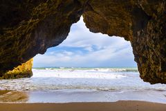 View through an arch of rocky cliff. At  Praia Dona Ana near Lagos city, Portugal Stock Image