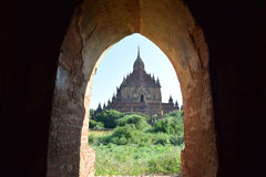 View through arch to Bagan temple, Myanmar. One of the thousands of temples that are spread across the plains of Bagan. One of the richest archaeological sites Royalty Free Stock Images
