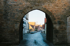 View through the arch to a beautiful street with traditional German houses in Rothenburg ob der Tauber in Germany Stock Image