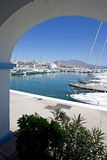 View through arch to Duquesa port and mountains Stock Photography