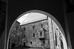 View through an arch towards a stone castle courty Stock Image
