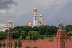View on Archangelsky and Uspensky Cathedral behind the Kremlin wall in Moscow against the background of the cloudy sky.  Stock Image