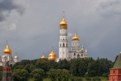 View on Archangelsky and Uspensky Cathedral behind the Kremlin wall in Moscow against the background of the cloudy sky.  Stock Photography