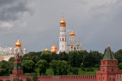 View on Archangelsky and Uspensky Cathedral behind the Kremlin wall in Moscow against the background of the cloudy sky.  Royalty Free Stock Photo