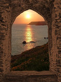 View through arched castle window to sunset coastal landscape, c. Ornwall, uk stock photography