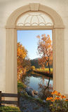 View through arched door, autumnal lake shore Royalty Free Stock Photography