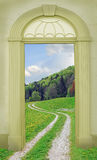 View through arched door, hiking path in hilly landscape Royalty Free Stock Image