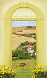 View through arched door, hilly landscape and little village Stock Image
