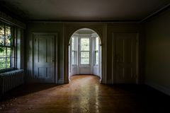 Arched Opening & Bay Window - Abandoned Tioranda Mansion and Hospital - New York. A view of a an arched opening leading to a bay window in a hardwood lined room royalty free stock photo