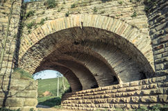 View of the arcs of the old historic stone bridge. Located in Ukraine Royalty Free Stock Photography