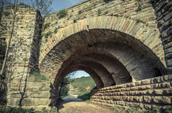 View of the arcs of the old historic stone bridge. Located in Ukraine Royalty Free Stock Photos