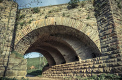 View of the arcs of the old historic stone bridge. Located in Ukraine Royalty Free Stock Photo
