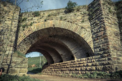 View of the arcs of the old historic stone bridge. Located in Ukraine Stock Photos