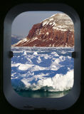 View of the Arctic through a ships porthole. Davy Sound in King Oscars Fjord on the east coast of Greenland viewed through a ships porthole Royalty Free Stock Photos
