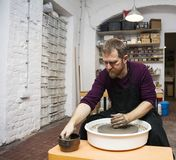 Male artist makes clay pottery on a spin wheel. View at an artist makes clay pottery on a spin wheel stock photos